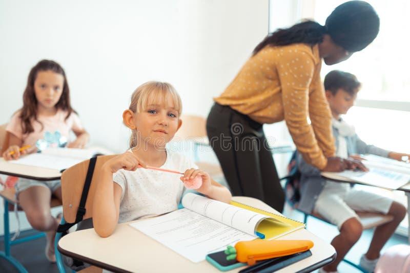 Mooie blauw-eyed schoolmeisjezitting bij het bureau in klaslokaal royalty-vrije stock foto
