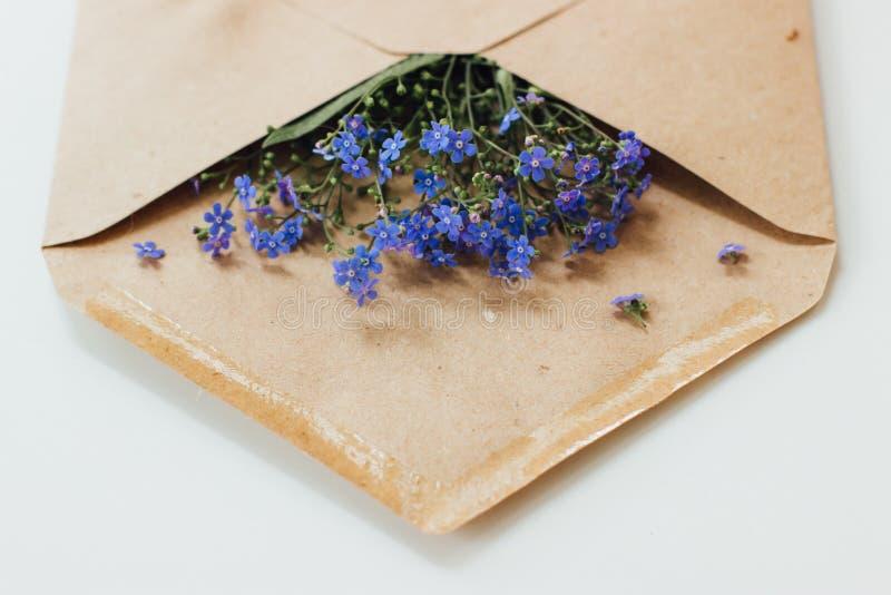 Mooie blauwe bloemen in een postenvelop royalty-vrije stock afbeeldingen