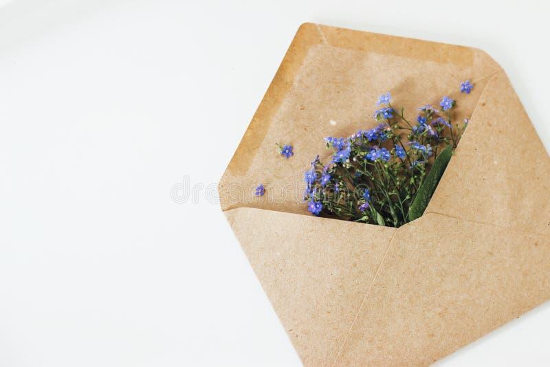Mooie blauwe bloemen in een postenvelop royalty-vrije stock afbeelding