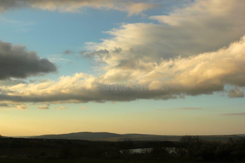 Mooie blauwe hemel en vage roze en witte wolken bij zonsondergang stock fotografie