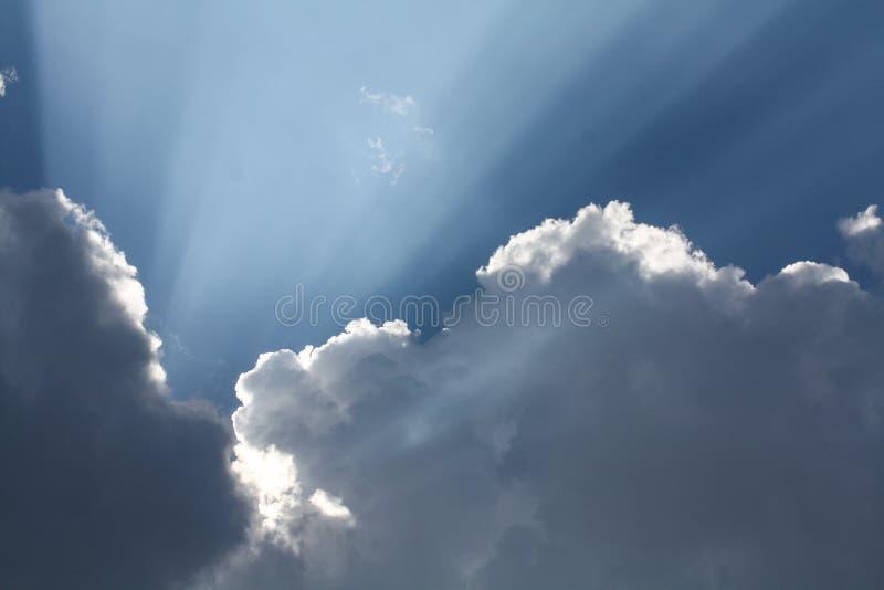 Mooie blauwe hemel met zonstralen die uit de wolken, hemel komen Witte krullende wolken, goddelijk licht De stralen royalty-vrije stock afbeelding
