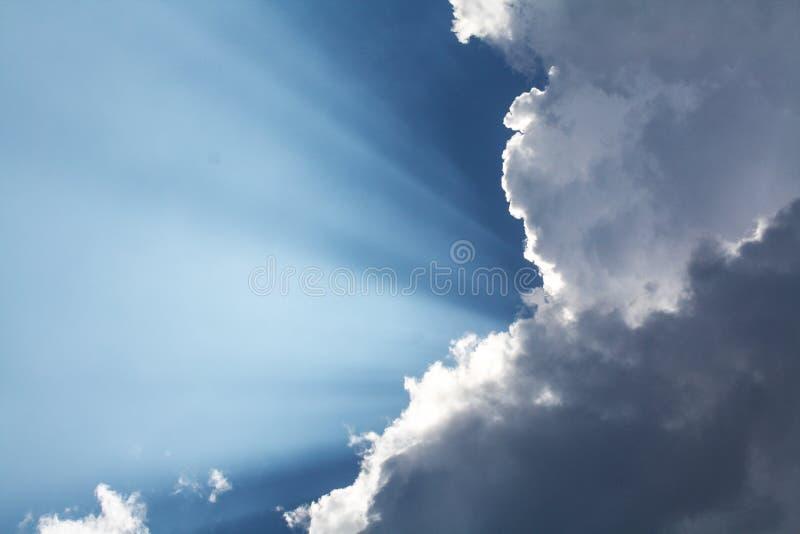 Mooie blauwe hemel met zonstralen die uit de wolken, hemel komen Witte krullende wolken, goddelijk licht De stralen stock afbeeldingen