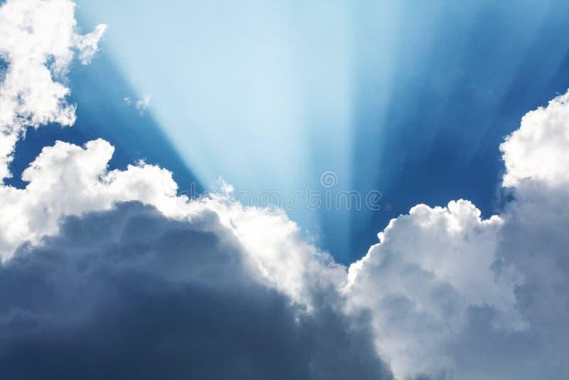 Mooie blauwe hemel met zonstralen die uit de wolken, hemel komen Witte krullende wolken, goddelijk licht De stralen stock afbeelding