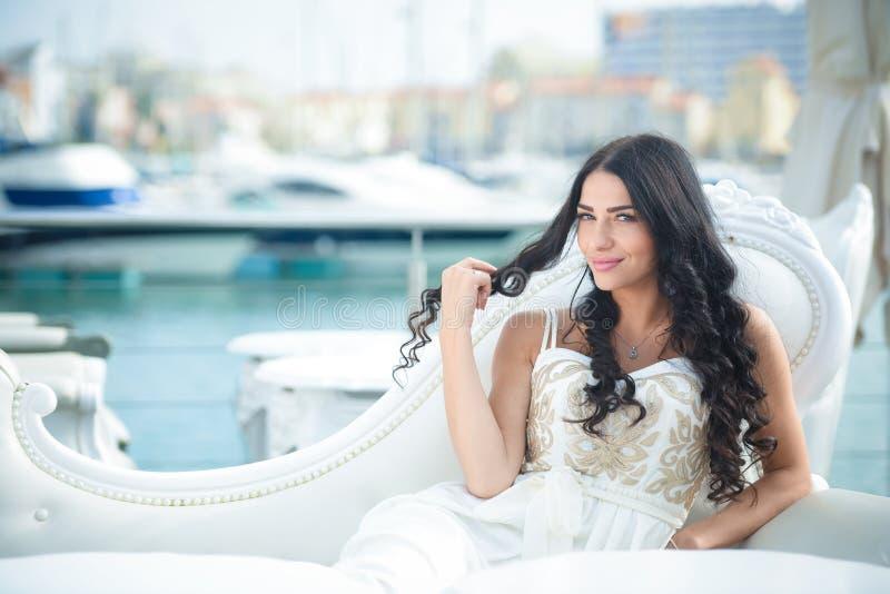 Mooie blije vrouw in elegante kleding op zonnige dag bij jachthaven stock fotografie