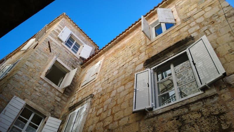 Mooie blinden in Budva, Montenegro De mening van beneden naar boven over een kleine straat van de oude stad stock foto's
