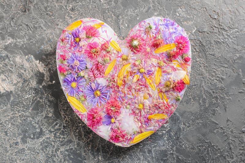 Mooie bloemen die in hart-vormig ijs op grijze achtergrond, hoogste mening worden bevroren stock foto