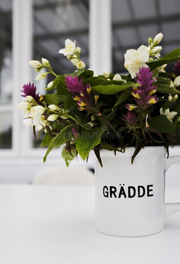 Mooie bloemen in een witte pot met het schrijven stock fotografie
