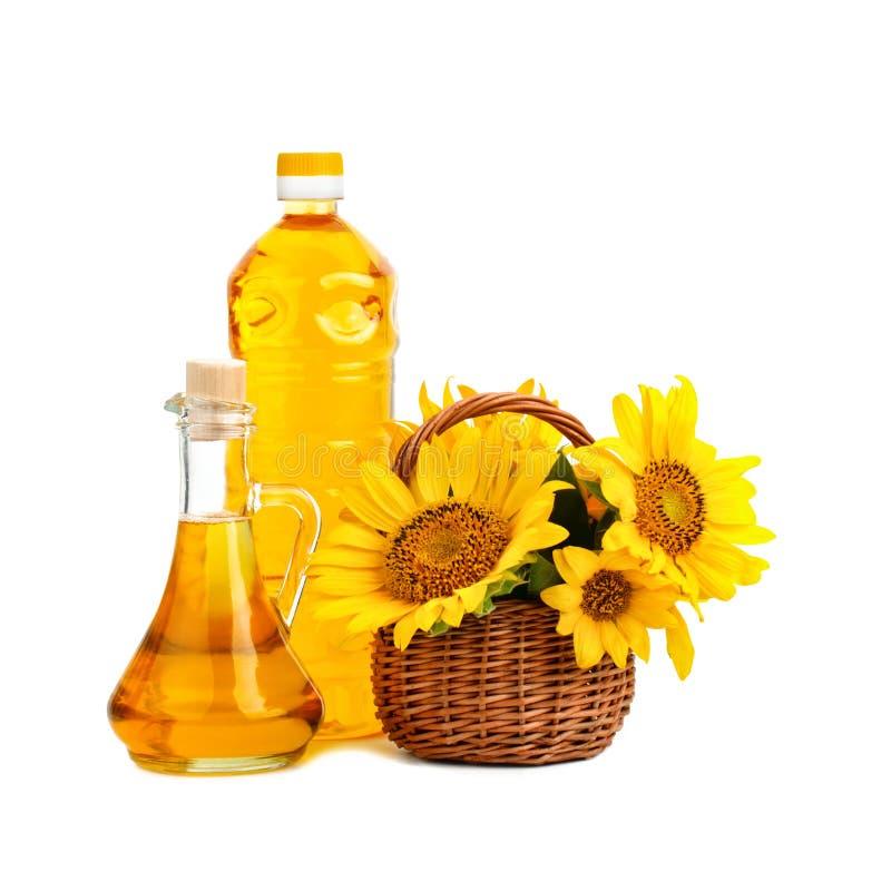 Mooie bloemen van zonnebloemen in een rustieke mand en zonnebloemolie op een witte achtergrond stock foto