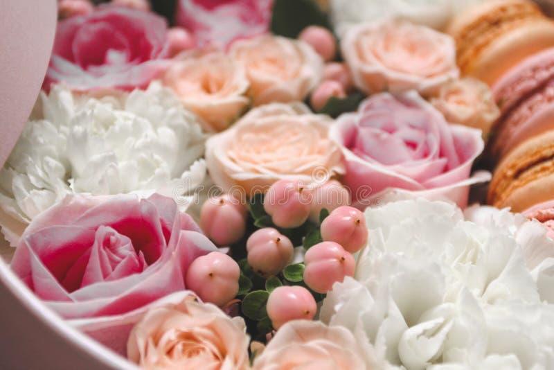 Mooie bloemenachtergrond in de Doos met de makarons bovenop de achtergrond stock foto