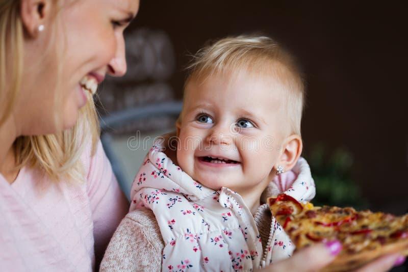 Mooie blond weinig babymeisje in het mooie witte kleding bijten op stuk van smakelijke pizza royalty-vrije stock afbeelding