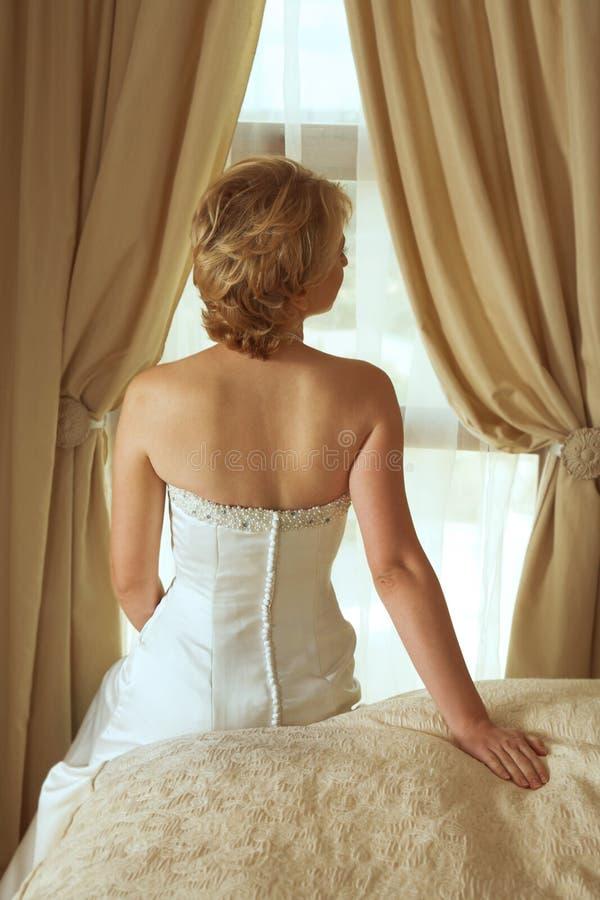 Mooie blonde bruid in de kleding van de satijnparel royalty-vrije stock fotografie