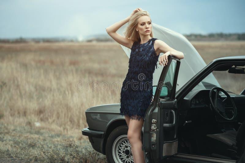 Mooie blonde dame in de luxueuze donkerblauwe avondjurk die van de lovertjeleeswijzer zich bij haar oude auto met open kap bevind royalty-vrije stock foto's