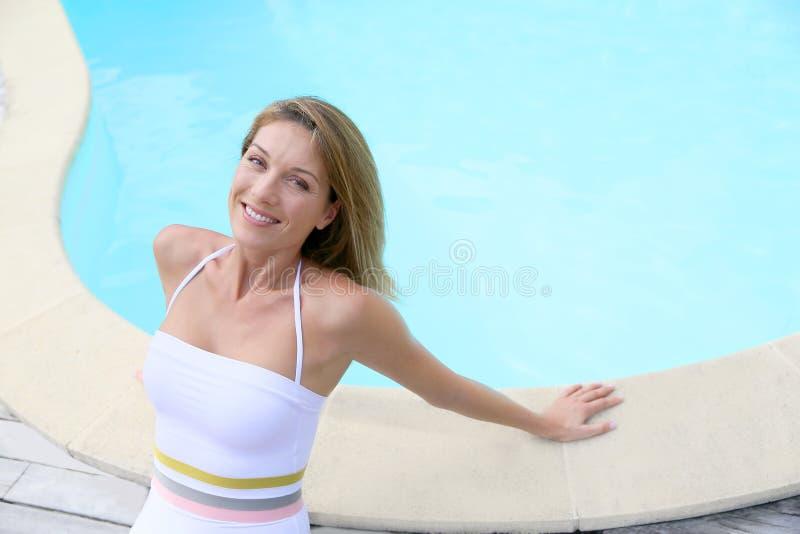 Mooie blonde dame door de pool royalty-vrije stock foto