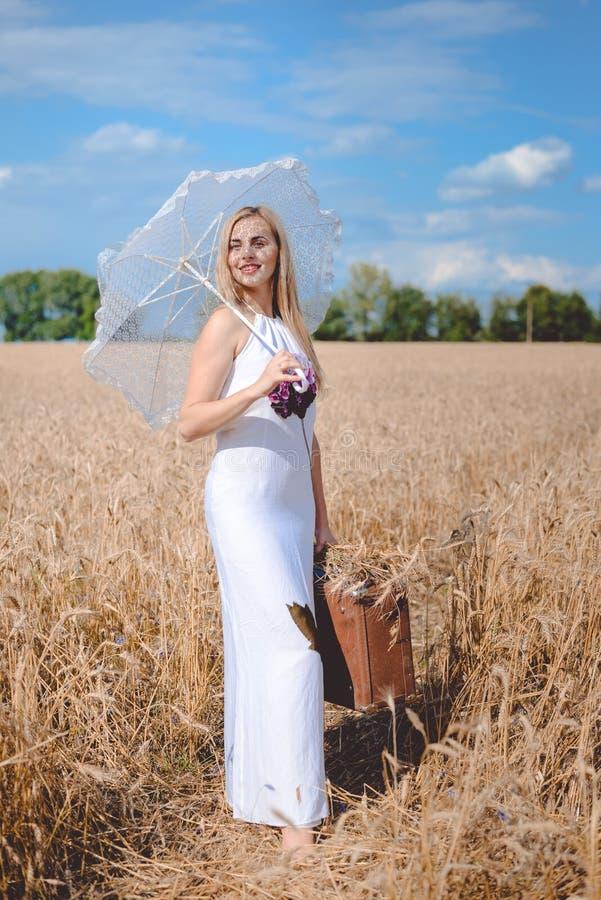 Mooie blonde dame met paraplu en koffer royalty-vrije stock afbeeldingen