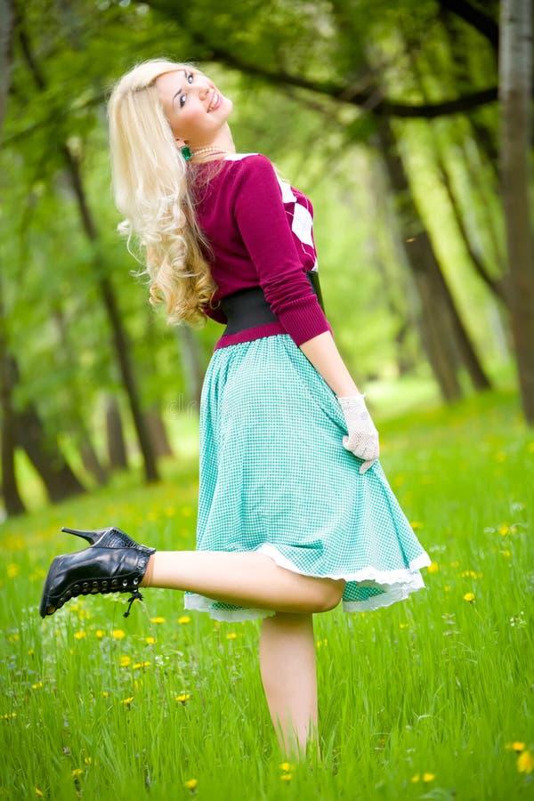 Mooie blonde dragende lange rok in de zomerpark royalty-vrije stock foto's