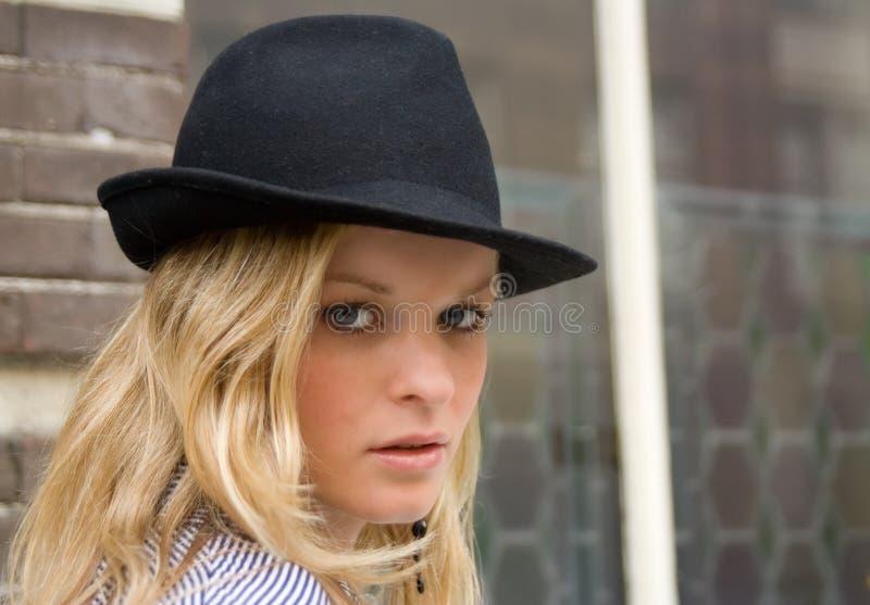 Mooie blonde in een zwarte hoed stock foto
