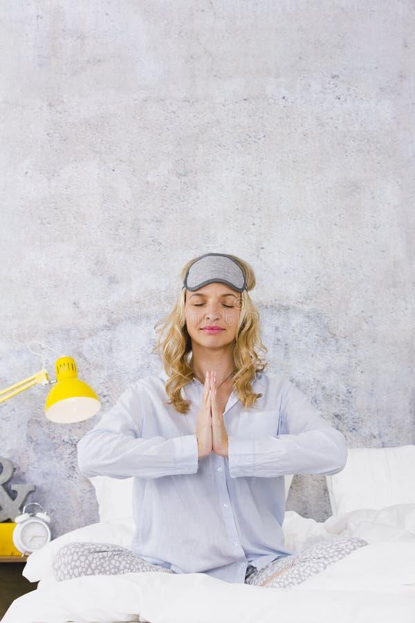 Mooie blonde en jonge vrouw die, die slaapmasker, zitting in bed dragen en yogaoefeningen in de ochtend doen royalty-vrije stock foto's