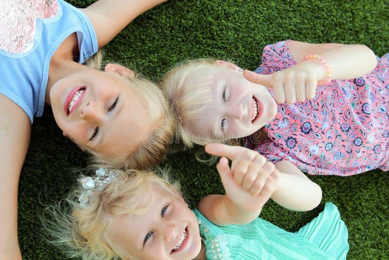 Mooie blonde glimlachende meisjes die op het gras op een de zomerdag liggen stock foto's
