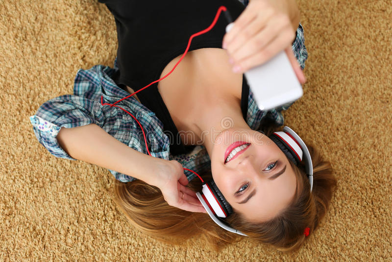 Mooie blonde glimlachende vrouw die op tapijtvloer liggen die hea dragen stock afbeeldingen