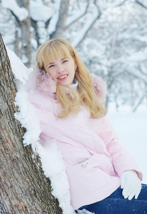 Mooie blonde jonge die vrouw tegen aan sneeuwboom wordt geleund stock foto