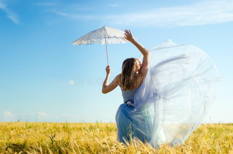 Mooie blonde jonge vrouw die lange blauwe balkleding draagt en witte kantparaplu houdt die omhoog leunend op tarwegebied stock foto