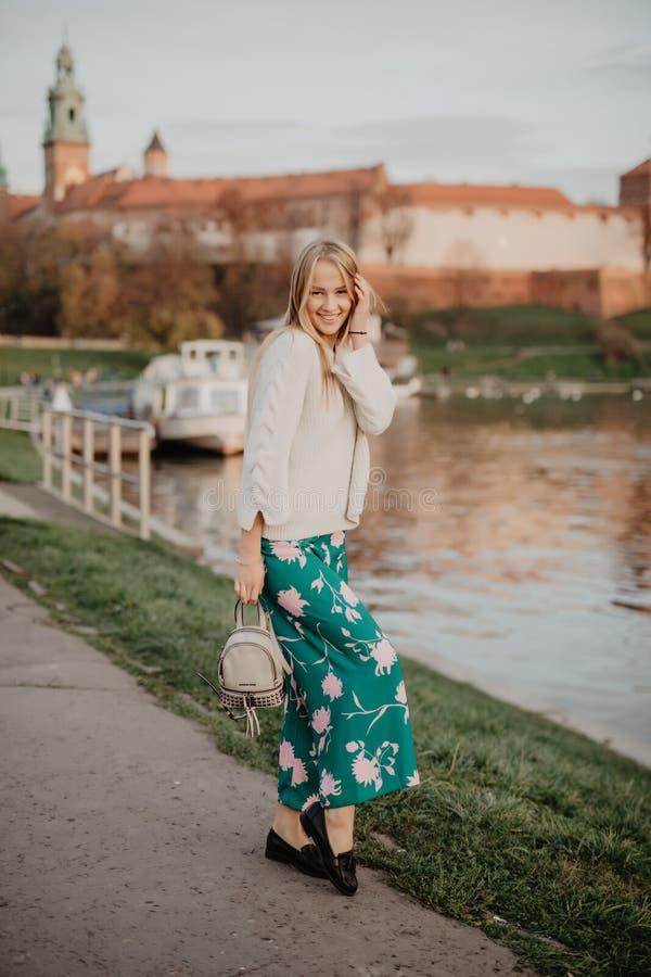 Mooie blonde jonge vrouw die naast de rivier bij zonsondergang lopen Haar haar die in de wind blazen royalty-vrije stock afbeelding
