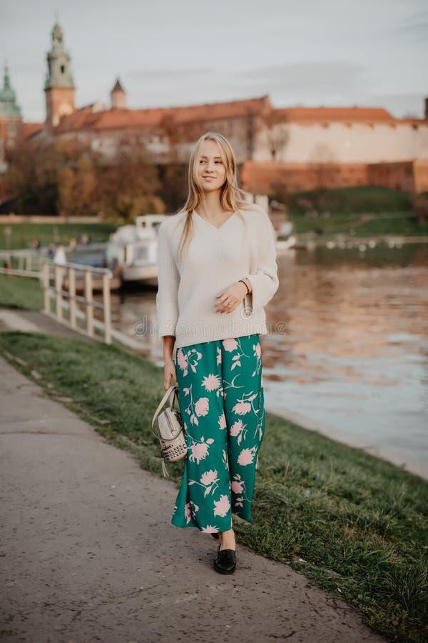Mooie blonde jonge vrouw die naast de rivier bij zonsondergang lopen Haar haar die in de wind blazen stock afbeelding