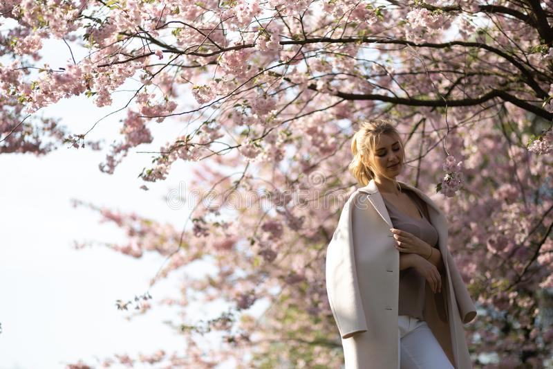 Mooie blonde jonge vrouw die in Sakura Cherry Blossom-park in de Lente van aard en vrije tijd genieten tijdens haar die reizen stock afbeelding