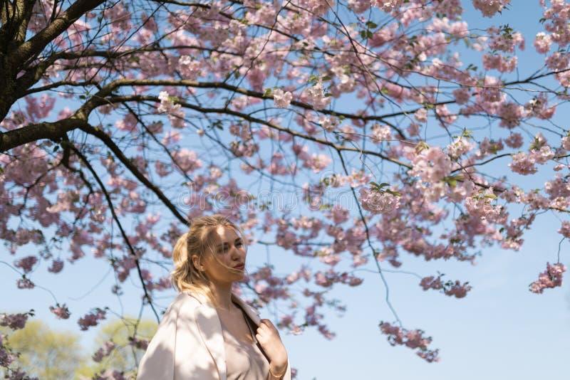 Mooie blonde jonge vrouw die in Sakura Cherry Blossom-park in de Lente van aard en vrije tijd genieten tijdens haar die reizen stock foto's