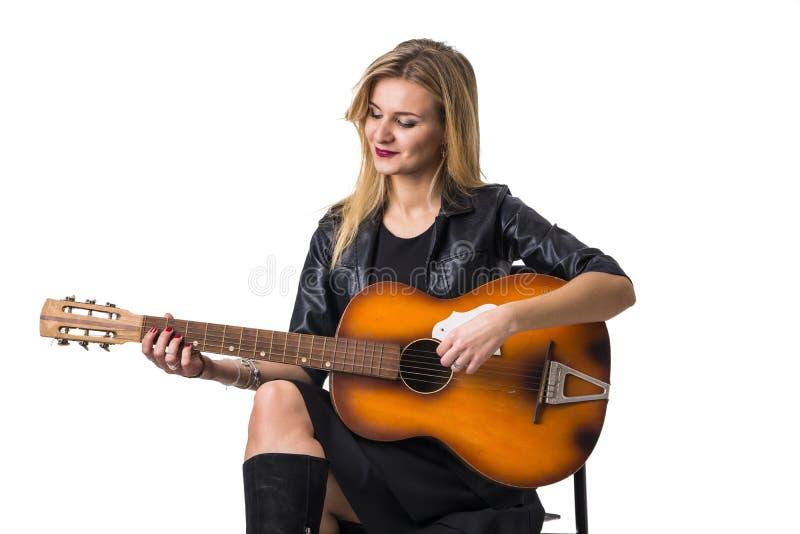 Mooie blonde jonge vrouw het spelen gitaar stock afbeelding