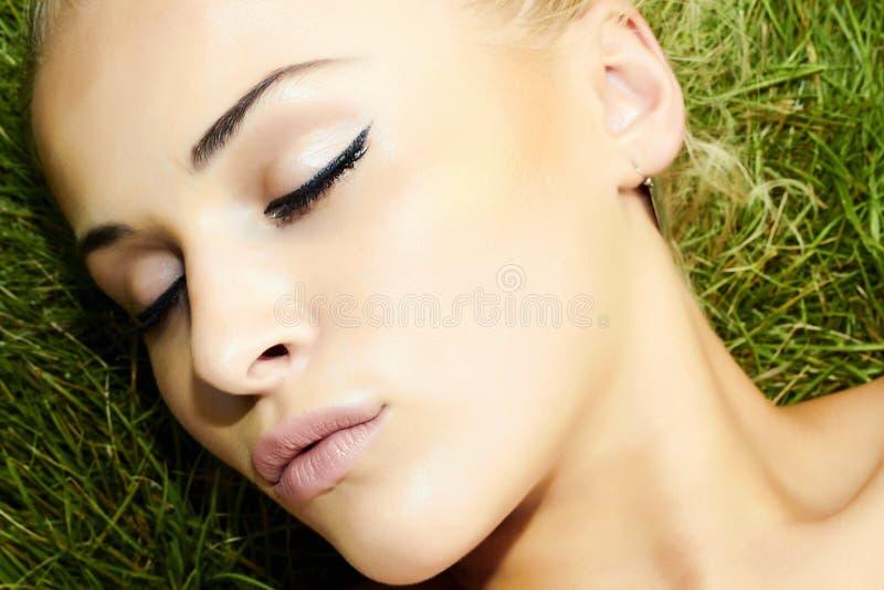 Mooie blonde meisjesslaap op groen gras. schoonheidsvrouw stock fotografie