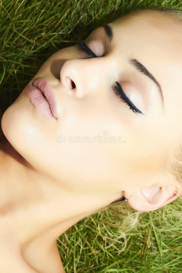 Mooie blonde meisjesslaap op groen gras. schoonheidsvrouw stock afbeelding
