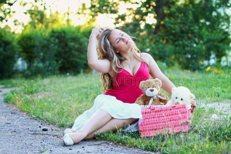 Mooie blonde meisjeszitting op het gras stock afbeelding
