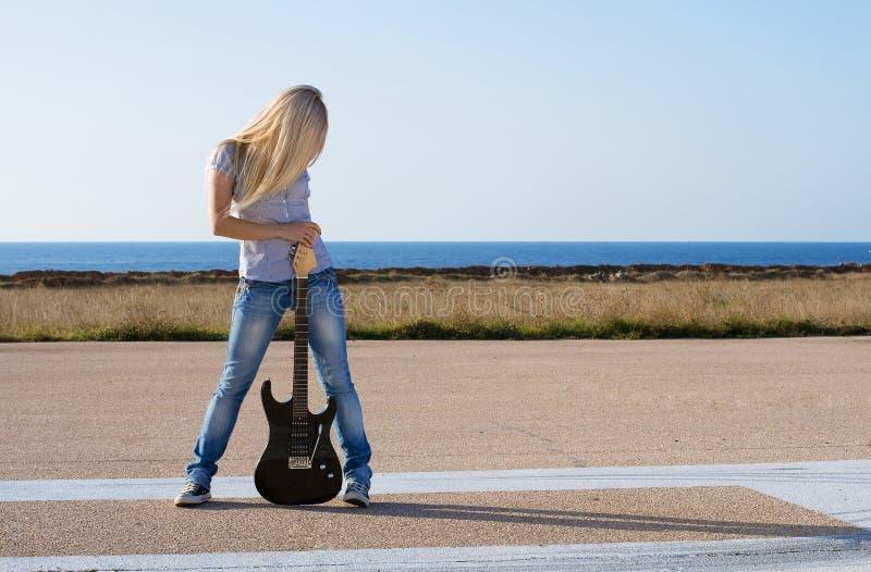 Mooie blonde met een gitaar stock fotografie