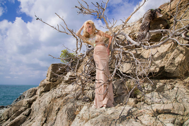 Mooie blonde sexy vrouw met lange benen in fantastische kristalkleding die zich op rotsen bevinden die het blauwe overzees overzi stock foto