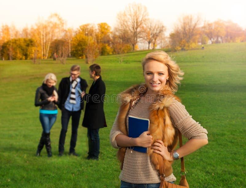 Mooie blonde student met vrienden stock foto
