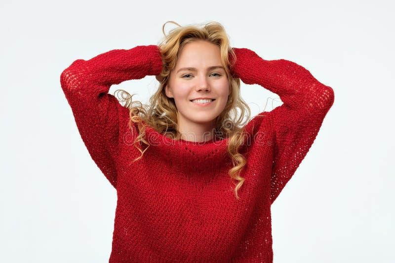 Mooie blonde tiener die ruim in rode sweater glimlachen stock afbeeldingen