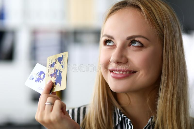 Mooie blonde volwassen Kaukasische vrouw in bureaugreep twee creditcards stock afbeelding
