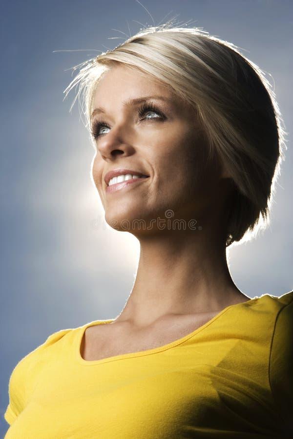Mooie blonde vrouw backlit door de zon stock afbeelding