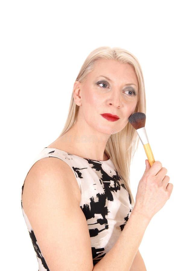 Mooie blonde vrouw die haar make-up met een borstel bevestigt royalty-vrije stock afbeeldingen
