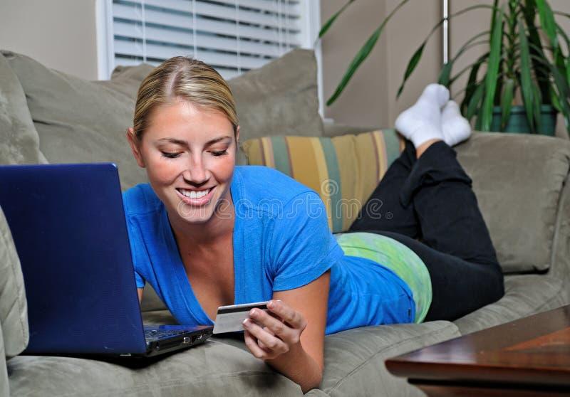 Mooie blonde vrouw die laptop op laag met behulp van royalty-vrije stock afbeelding