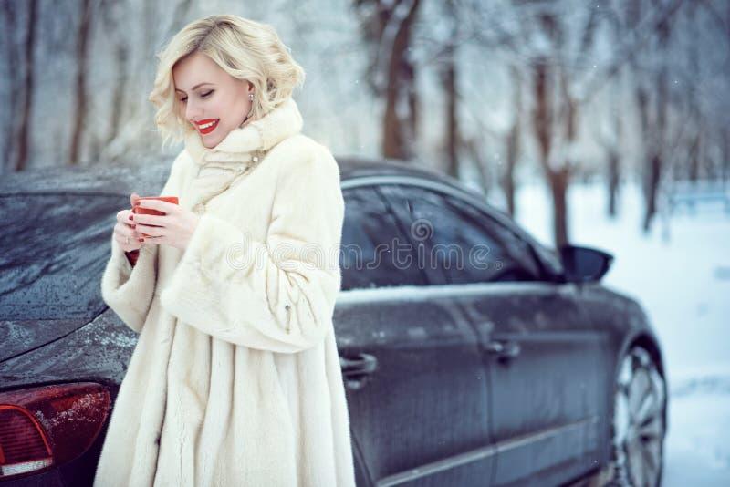 Mooie blonde vrouw die in luxueuze witte bontjas hete koffie op sneeuw de winterdag drinken stock foto