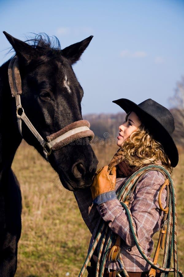 Mooie blonde vrouw die zich door paard bevindt royalty-vrije stock foto's
