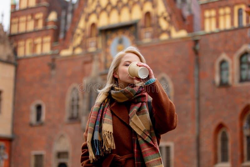 Mooie blonde vrouw drinkt koffie in de oude stad royalty-vrije stock foto