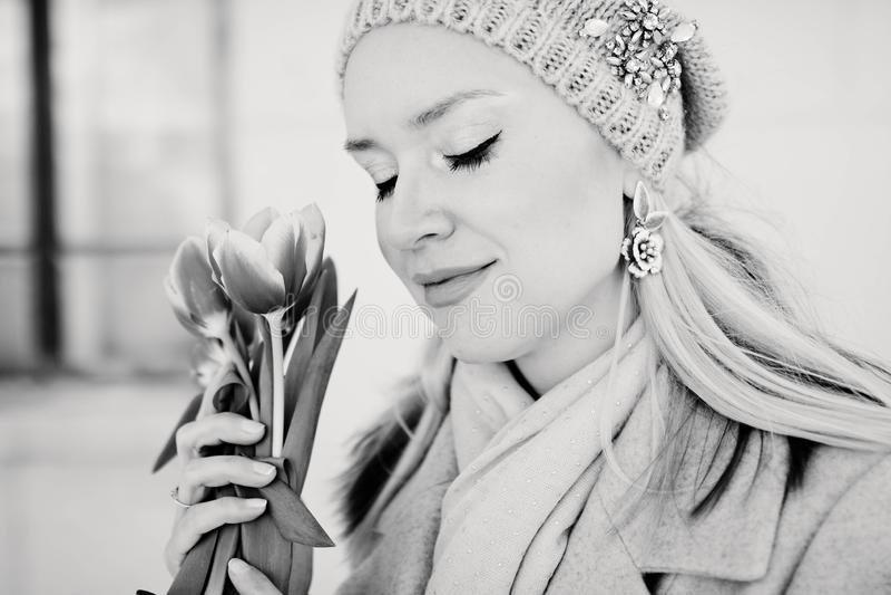 Mooie blonde vrouw in een gebreide hoed met tulpenbloemen De Zwart-witte foto van Peking, China stock fotografie