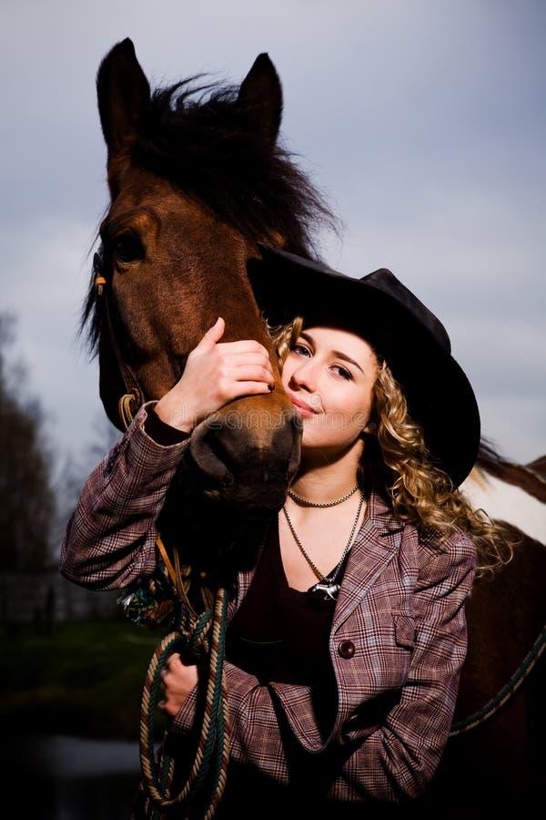 Mooie blonde vrouw in een hoed die zich door paard bevindt stock foto's