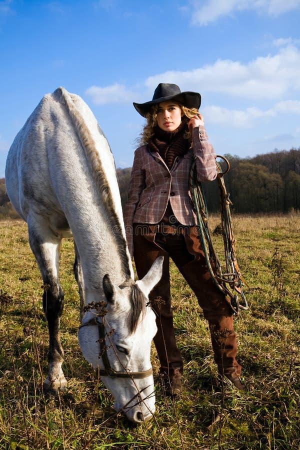 Mooie blonde vrouw in een hoed die zich door paard bevindt stock afbeeldingen