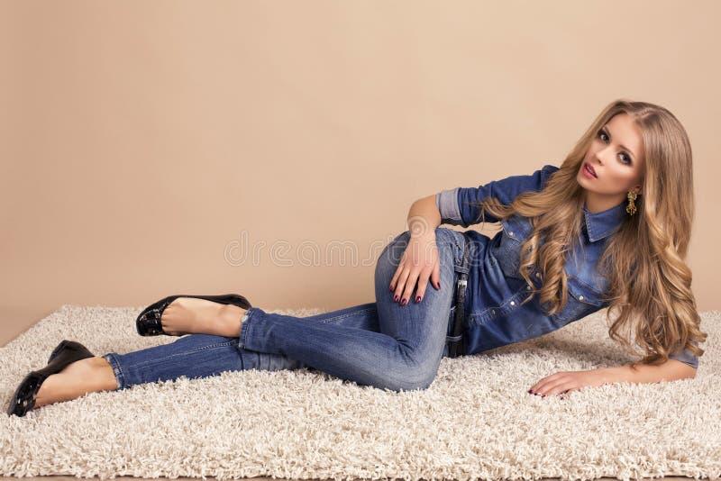 Mooie blonde vrouw in jeanskleren royalty-vrije stock foto's