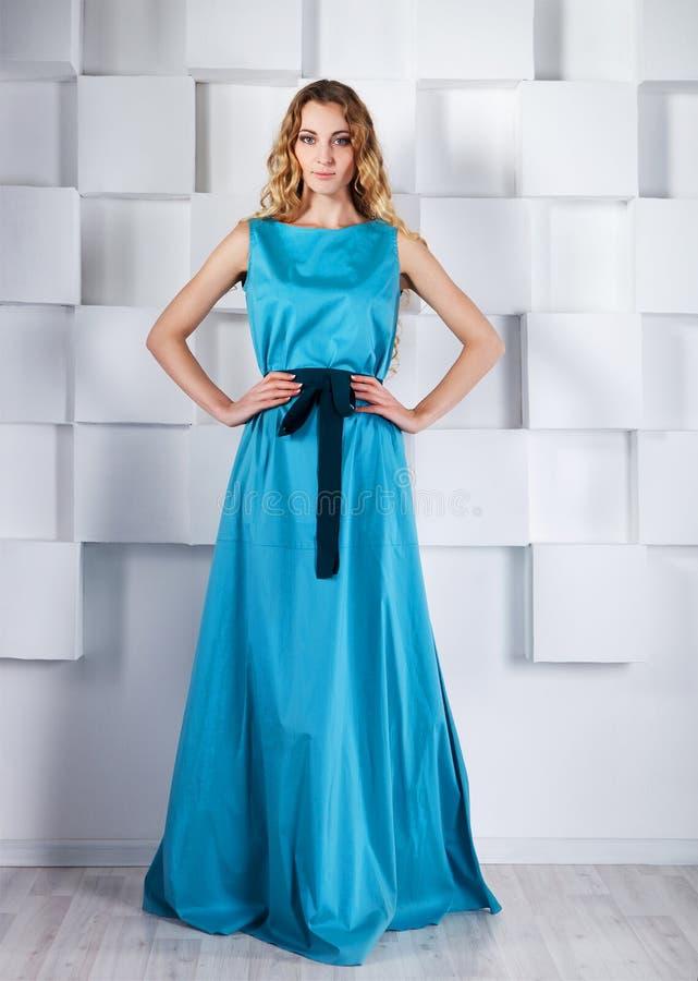 Mooie blonde vrouw in lange blauwe kleding stock foto's