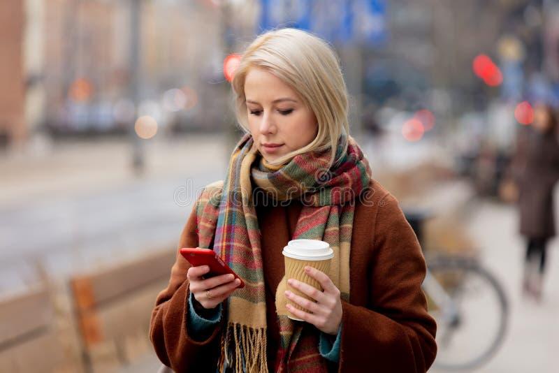 Mooie blonde vrouw met kop koffie met mobiele telefoon royalty-vrije stock afbeeldingen